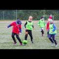 Dzieci grają w piłkę nożną na boisku.